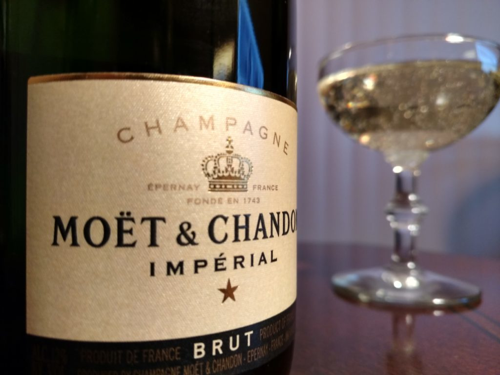 Pictured: Moet & Chandon Imperial Champagne label, with glass of champagne in background